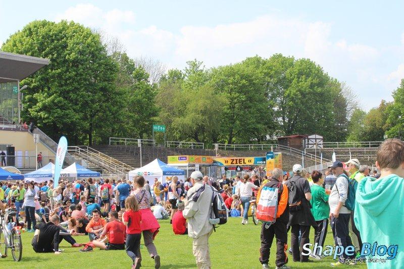 Läufer und Angehörige erholen sich auf der Wiese im Heinz-Steyer-Stadion